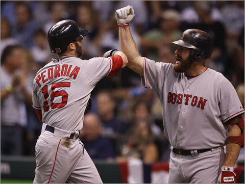 Red Sox second baseman Dustin Pedroia (left) and Kevin Youkilis (right) celebrated after Pedroia's home run in the first inning.