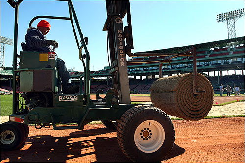 A machine brought a roll of Kentucky bluegrass sod to the infield, which is being replaced after 86 home games of wear and tear.