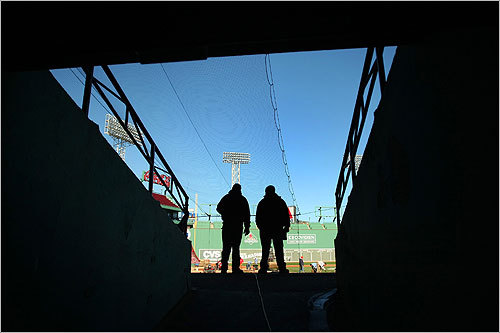 Workers surveyed the field at an entrance to the stands behind home plate.