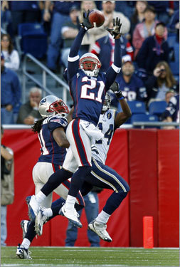 Patriots cornerback Delthea O'Neal (21) out-jumps Rams receiver Keenan Burton (14) as he is about to haul in his late fourth quarter interception.