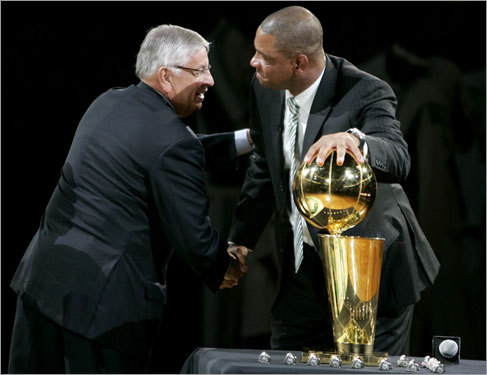 NBA Commissioner David Stern (left) shook hands withCeltics coach Doc Rivers (right)as Rivers touched the Larry O'Brien Trophy during the pregame celebration.