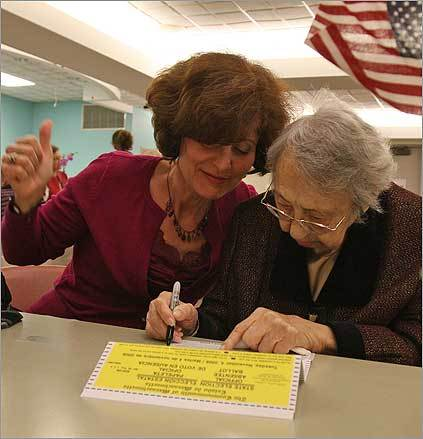 Residents at the Hebrew Rehabilitation Center in Roslindale cast their absentee ballots on Oct. 29 in a polling place-style atmosphere set up in the facility's basement. Interpreter Alexandra Dashevskaya gave a thumbs up as 107-year-old Tsilya Braz filled in the last entry on her ballot.