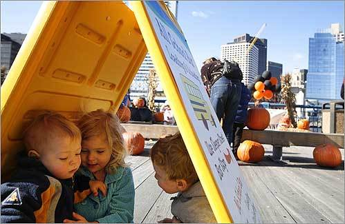 Isobel Farone, 3, of Roslindale, hid with her brother, Giovanni (left), 1, and her friend Cooper Kennedy, 3, of Brighton, under a promotional sign at the Fort Point Pumpkin Pageant at the Children's Museum in South Boston on Oct. 30.