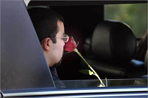 Anthony Fortunato, brother of US Army Specialist Stephen Fortunato, who was killed in Afghanistan on Oct. 13, sniffed at a rose during the funeral procession to St. Mary's Cemetery following Stephen Fortunato's funeral in downtown Beverly on Oct. 24.