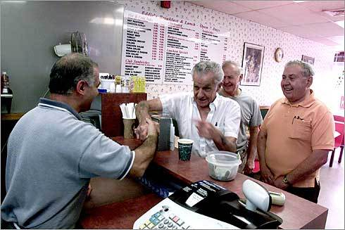 Eddie Cimen (left) greets 'Fat' Pellegrini, Roger Arsenault, and Ernie Pesky at his restaurant.