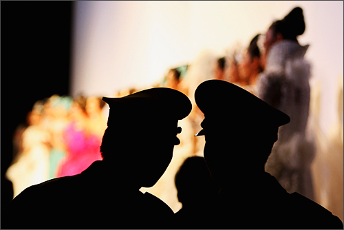 Two Chinese security guards watch the TSAI Meiyue Fashion Show S/S 2009 at China Fashion Week Spring/Summer Collection 2009 on November 7, 2008 in Beijing, China.