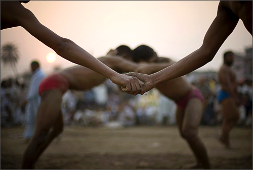 Pakistani wrestlers join their hands sharing the soil as part of a ritual before fighting during a local competition in Lahore, Pakistan, Saturday, Nov. 15, 2008.