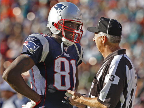 Patriots wideout Randy Moss has a laugh with side judge Joe Larrew (right) during a break in the action. He appeared to be talking about the penalty that was called on Miami a few plays before, on Moss's third touchdown catch of the game.