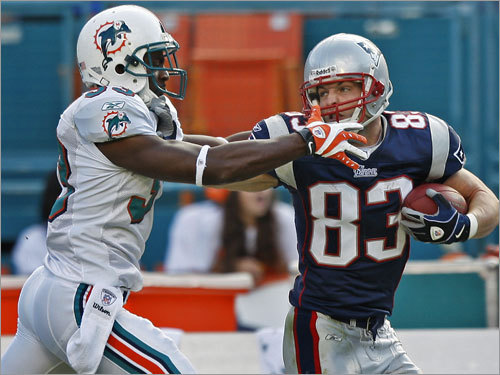 Wes Welker has his game face on as he stiff-arms Miami's Nathan Jones near the end of a 64-yard catch and run.