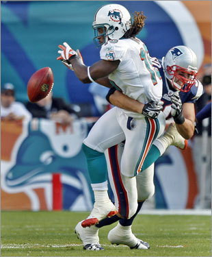 Dolphins WR Davone Bess can't hold on to a pass thanks to a hit by Patriots linebacker Mike Vrabel (right).