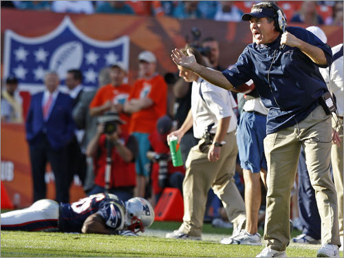 Patriots head coach Bill Belichick yells from the sidelines while DB James Sanders lies injured in the background.