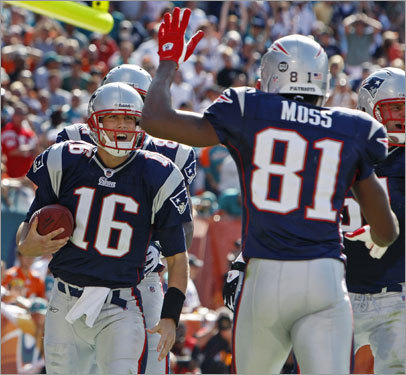 Patriots quarterback Matt Cassel (left) gets a hand from Randy Moss after his first quarter TD run.
