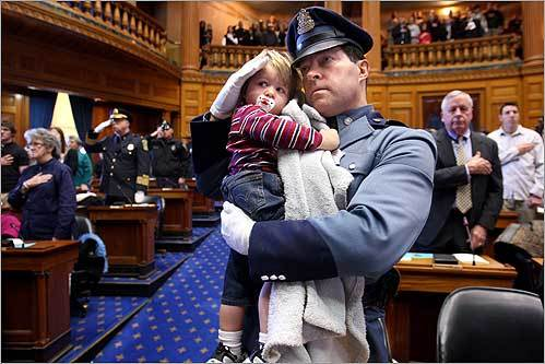 Trooper John Hanna saluteed during the national anthem with his son John Jr. while attending the 25th annual Trooper George Hanna Awards for Bravery in the House Chambers at the State House on Dec. 8. George Hanna was his brother and died in the line of duty in 1983.