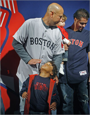 Pitcher Manny Delcarmen (right) holds his son Manny Delcarmen III, while modeling the alternate road jersey, while David Ortiz' son D'Angelo looks up at Red Sox manager Terry Francona (left), who is wearing the new primary road jersey.