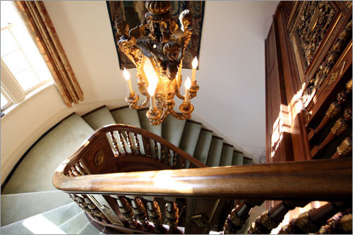 A look down the main staircase. The 12,000-square-foot house has original elegant details - ornate moldings, elaborate carvings, leaded glass panes, and gilded hardware.