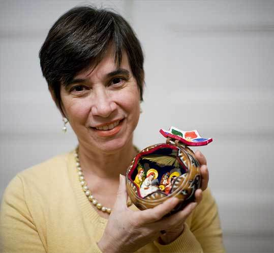 Norma Moreira with a calabash Nativity scene, from her native Ecuador, among the dozens of creches she has collected from around the world.