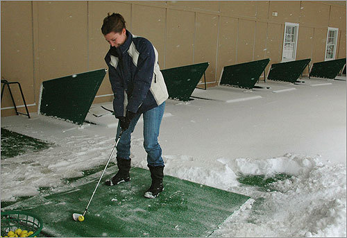 Despite heavy snow from Friday's storm, Kelly Jordan of Abington practiced her drive from a heated bay at the Harmon Club Rockland on Saturday.