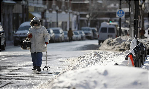 A woman with cane walked on the street on Dorchester Avenue.