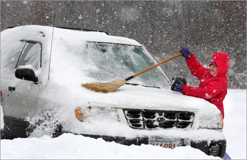 Chloe Bickford, 8, cleaned snow off a used car with a broom for the family business in Bolton on Sunday.