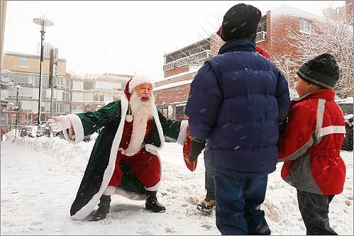 Santa greeted John, 7, and Karsten, 4, Steinke, of Arlington as they walked through the snowy streets of Harvard Square on Dec. 21. The Harvard Square Business Association sponsored Sparklefest 2008, which included a small parade with Santa and other candy-bearing well-wishers.