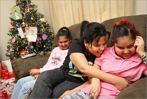 Providencia Aponte with her two daughters , Rhaissa (left), 16, and Natalie, 18, in their Lawrence home on Dec. 23. Both daughters have a genetic degenerative disease. Aponte called the Lazarus House to donate's Rhaissa's power wheelchair, after Rhaissa became unable to use it. The people of Lazarus then found out that the Aponte family could use help this Christmas and now they have presents under the tree.