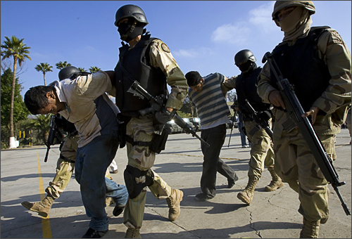 Mexican Army soldiers hold two suspects, arrested during an operation against drug smuggling and kidnapping gangs, after being presented to the press in Tijuana, Mexico on December 3, 2008. The Mexican Army ran an operation on a safe house after an anonymous call where they arrested four suspects and rescued two men.