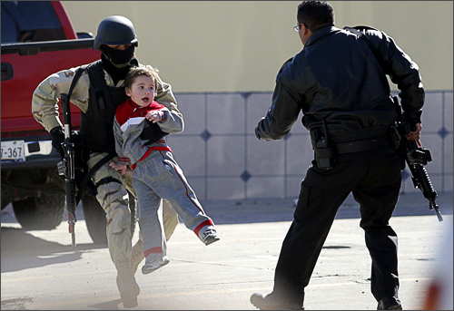 A policeman carries a child away during a gun battle in Tijuana, in Mexico's state of Baja California, January 17, 2008. A shootout after police agents moved in on a drug cartel group left four people injured and forced the emergency evacuation of a school in Tijuana, according to the local media.