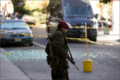 A Mexican soldier stands guard in front of an apartment building where a fragmentation grenade exploded in Mexico City on November 22, 2008. See more photography at Boston.com/photos