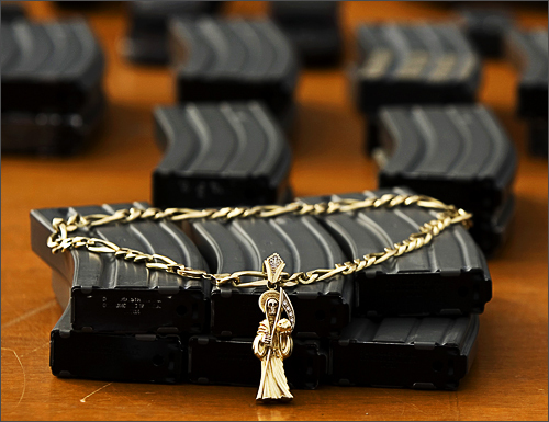 A Santa Muerte, or Grim Reaper pendant is displayed next to guns and ammunition magazines seized by the Mexican Army during a presentation of suspected gunmen and kidnappers to the press in Tijuana, Mexico on December 2, 2008. According to Mexican army authorities, the suspects could be involved in three days of violence that left 37 people dead in this border city plagued by warring drug gangs, including nine men found decapitated and four children who were caught in the middle of shoot-outs. See more photography at Boston.com/photos