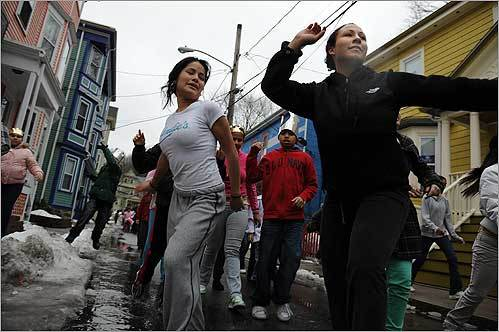 Maria Fernanda Novelle (left), 17, of Roslindale, and other members of the Spontaneous Celebrations Festival Arts group followed dance instructor Jennifer Bencosme's lead as they practiced on Dresden Street on Dec. 27 in Jamaica Plain for their First Night performance.