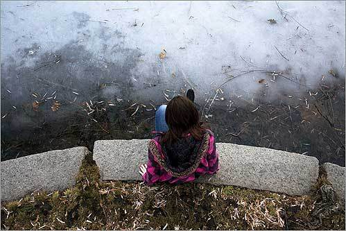 Stephanie Buonopane, of East Boston, touched the melted ice in the lagoon at the Public Garden in Boston on Dec. 28.