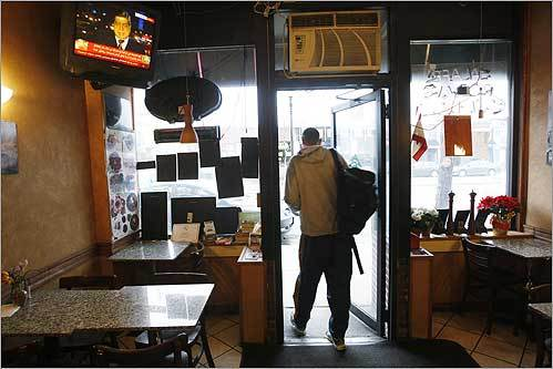 A television is tuned to Al Jazeera as Tahir Hussain, a Muslim who recently completed a pilgrimage to Mecca, picked up food at Reef Cafe in Allston on Dec. 29.