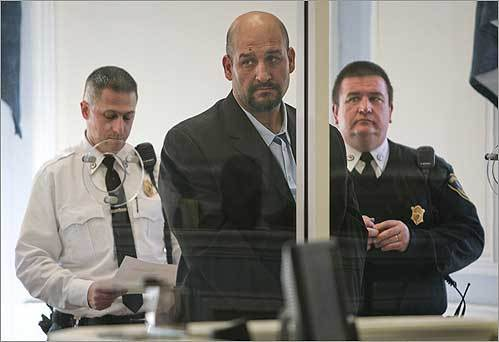 Daniel Villa (center), the athletic director at Walpole's high school and a former Patriots lineman, stood behind a partition during his arraignment in Wrentham District Court on sexual assault charges on Dec. 30.