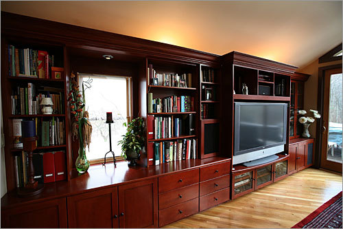 Cherry cabinets, with built-in connections for a media center, line one wall of the great room.