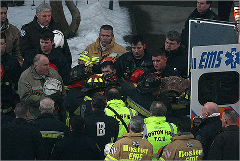 Firefighters solemnly looked on at the tragic scene as the body of one firefighter is put into an ambulance.