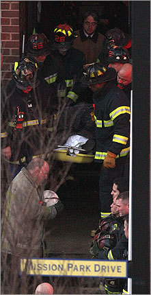 The body of a Boston firefighter was carried out of the Huntington Ave. building where Ladder 26 crashed.