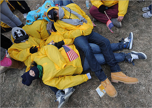 A group of students piled on top of each other to keep warm while waiting for the inauguration ceremony to begin.