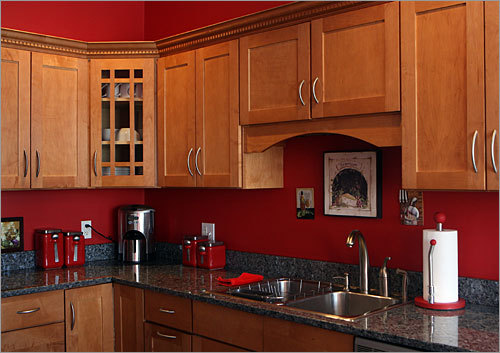The rectangular kitchen, clad in cherry red paint, easily absorbs a