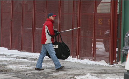 A member of the Red Sox staff brings a hockey stick into Fenway Park on an ice-cold Friday morning.