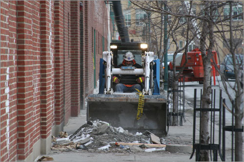 A construction crew cleans up around Fenway Park this morning.