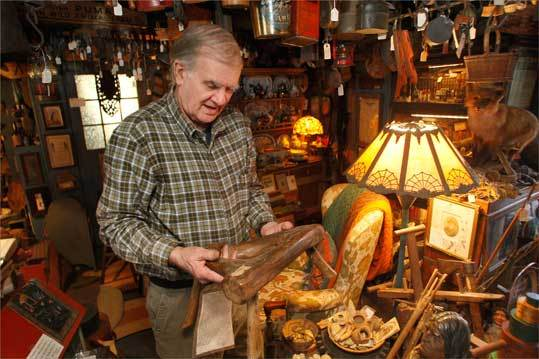Hingham historian John Richardson holding a 17th-century milking stool made from a tree root by Samuel Lincoln's son, Samuel Lincoln Jr.