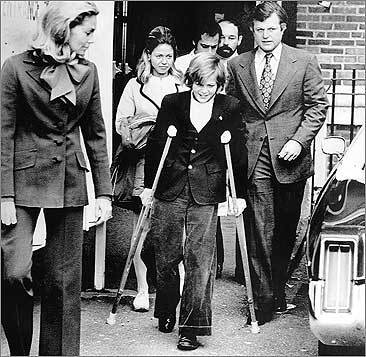 Teddy Kennedy Jr. walks with the aid of crutches and an artificial limb as he leaves Georgetown Hospital in Washington in 1973, accompanied by his parents.