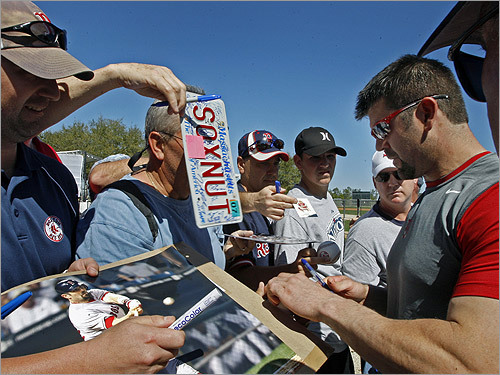 After the workout, Varitek (right) signed some autographs for eager fans, including photos of himself in action, and even a Massachusetts license plate that read 'SOXNUT'.