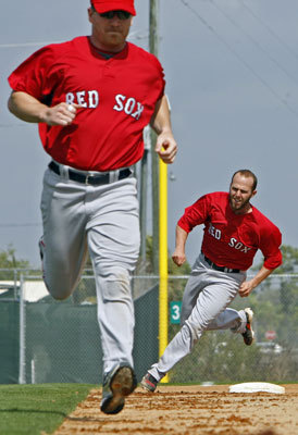 Red Sox second baseman Dustin Pedroia rounds third, as teammate J.D. Drew heads for home plate in front of him during a base running drill on Thursday.