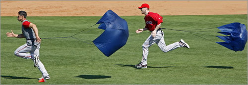 The Red Sox had the parachute devices out at the end of Friday's workout, and Jacoby Ellsbury (left) and Jason Bay (right) are shown as they used them in their running drills.