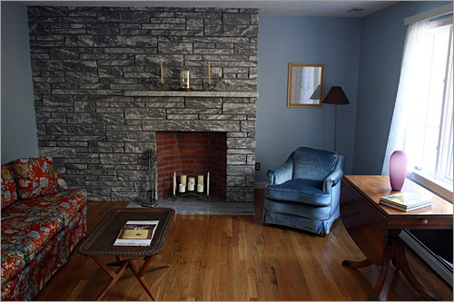 To the right of the entry is the living room, pale blue in color, with a working fireplace faced with gray and white bricks.