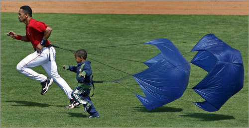 The Red Sox regulars took a turn at the end of Sunday's workout using the parachute devices that provide resistance as they do their wind sprints, and shortsop Julio Lugo (left) was joined by his three-year-old son Julio as he took part.