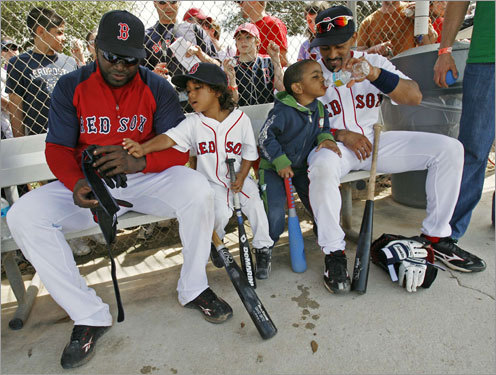 David Ortiz (left) sits with his 4-year old son D'Angelo as teammate Julio Lugo watches his 3-year old son, Julio Alejandro, in the dugout.