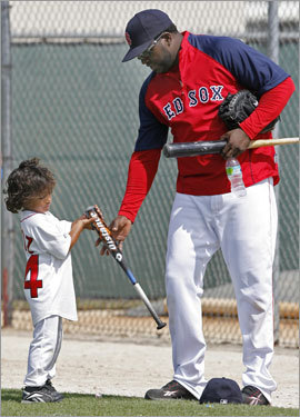 David Ortiz (right) hands his 4-year-old son D'Angelo his bat during spring training workouts