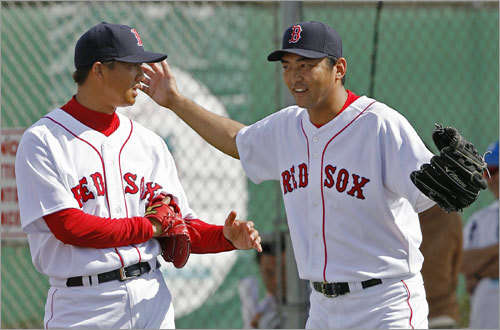 Hideki Okajima (left) talks with new teammate Takashi Saito during workouts.